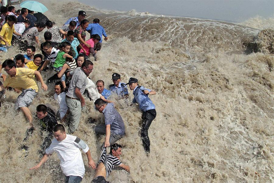 Местные жители спасаются отприливной волны нареке Цяньтан вгороде Хайнин. © China Daily/Reuters