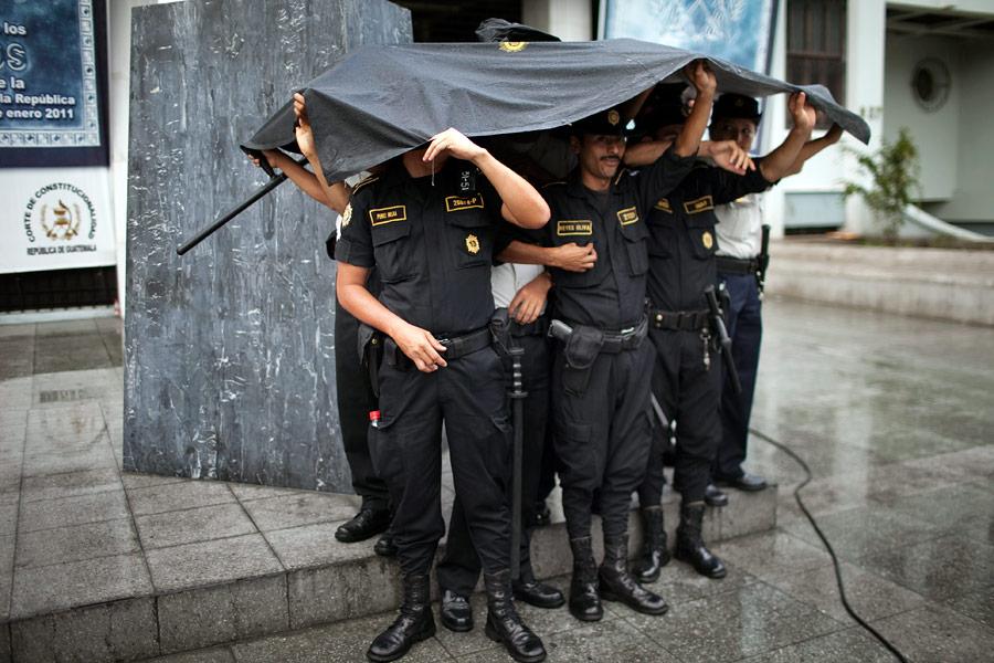 Гватемальские полицейские прячутся отдождя. © Rodrigo Abd/AP Photo