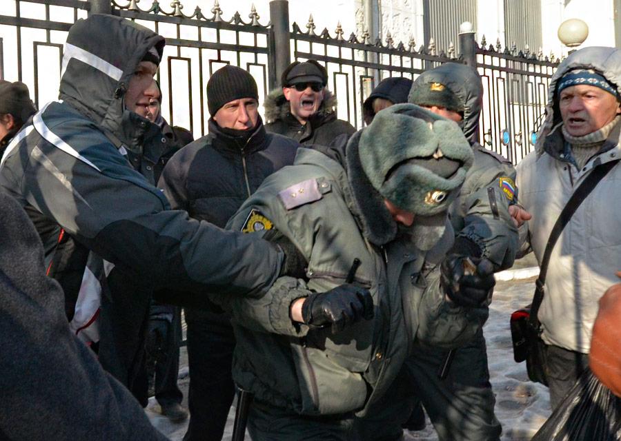 Сотрудник полиции пытается уклонится отгруппы митингующих наакции протеста «Зачестные выборы» воВладивостоке 24декабря 2011 года. © Yuri Maltsev/Reuters