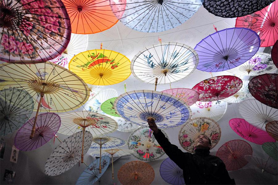 Продавец бумажных зонтиков нарынке вгороде Сиань, Китай. © Rooney Chen/Reuters