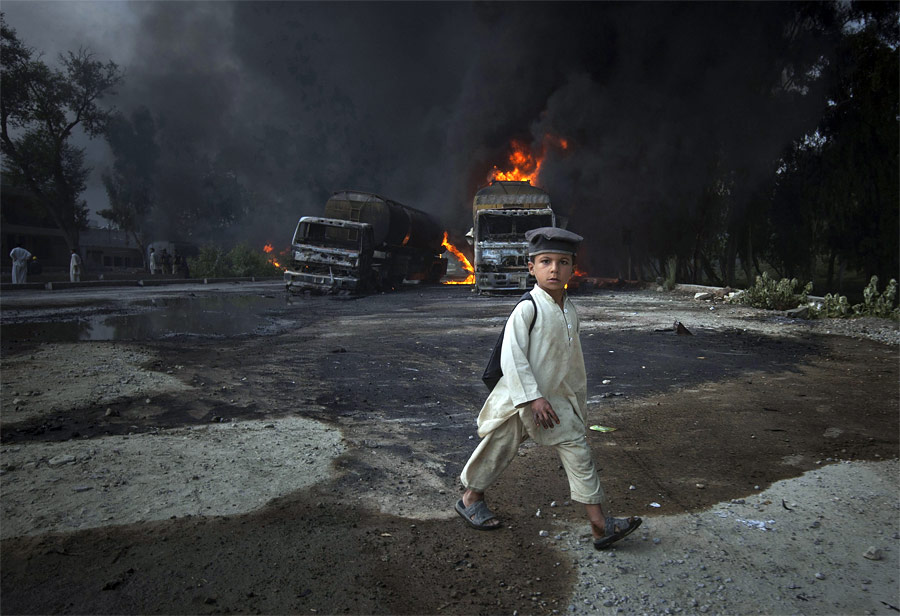 Пакистанский школьник идет мимо взорванных автоцистерн НАТО вНовшере. © Adrees Latif/Reuters