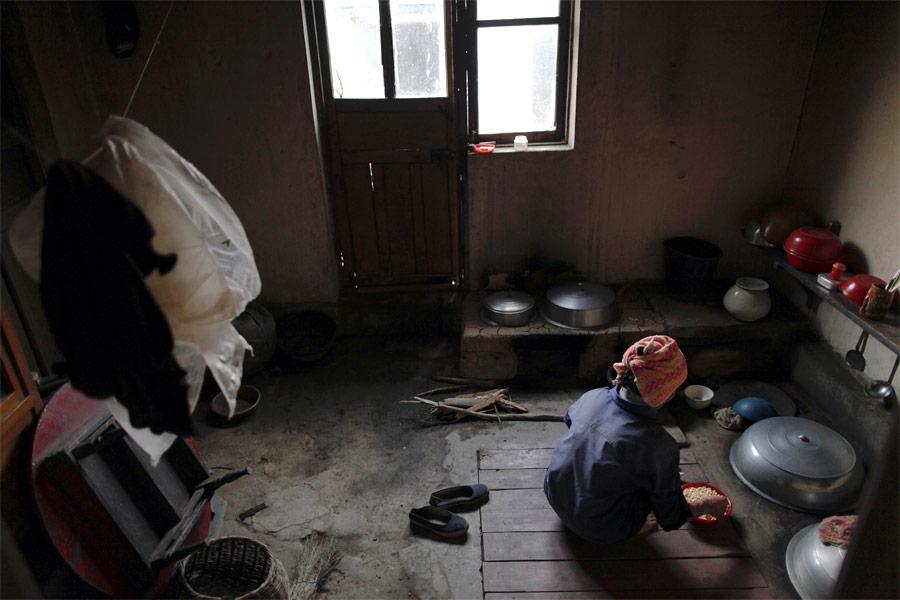 Женщина готовит еду всвоем доме вколхозе Сокса-Ри. © Damir Sagolj/Reuters