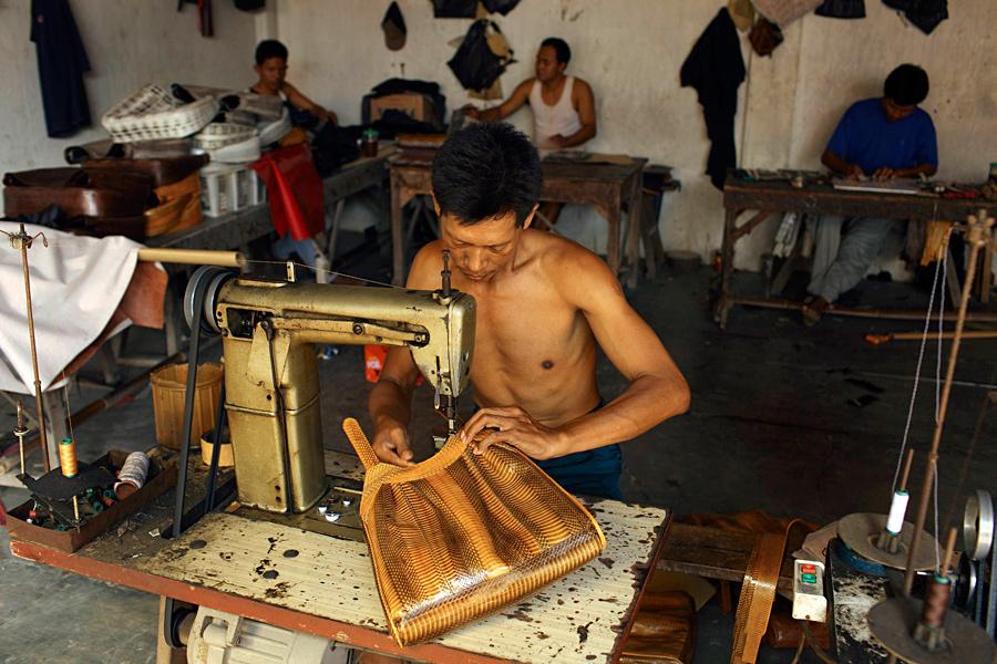 Рабочий шьёт сумку из змеиной кожи на фабрике в городе Пекалонган, провинция Центральная Ява, Индонезия.