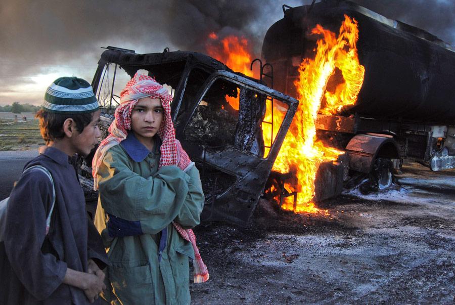 Школьники стоят возле горящих бензовозов впакистанском районе Болан Белуджистан. © Amir Hussain/Reuters