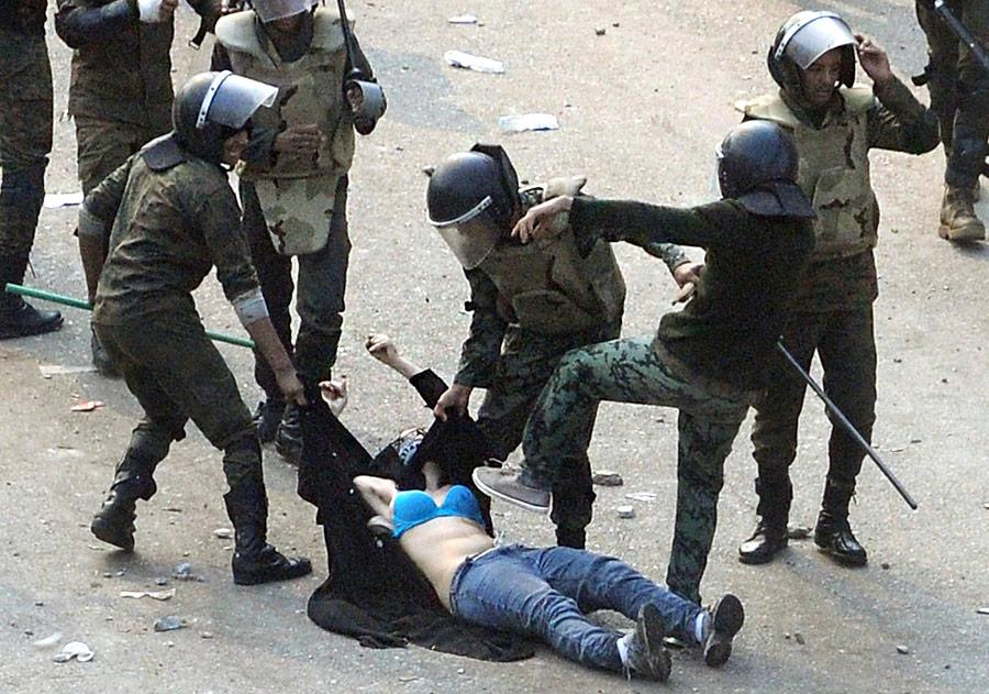 Полицейские избивают женщину входе столкновения сманифестантами вКаире. © Reuters