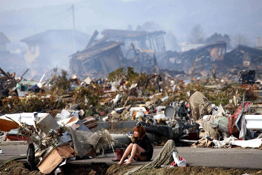 Женщина плачет надороге посреди разрушенном землетрясением ицунами города Натори вЯпонии. © Asahi Shimbun/Reuters