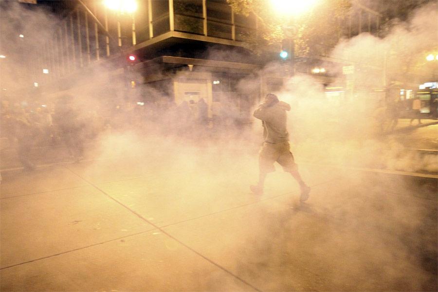 Участник акции Occupy Wall Street в Окленде убегает от слезоточивого газа. © Stephen Lam/Reuters