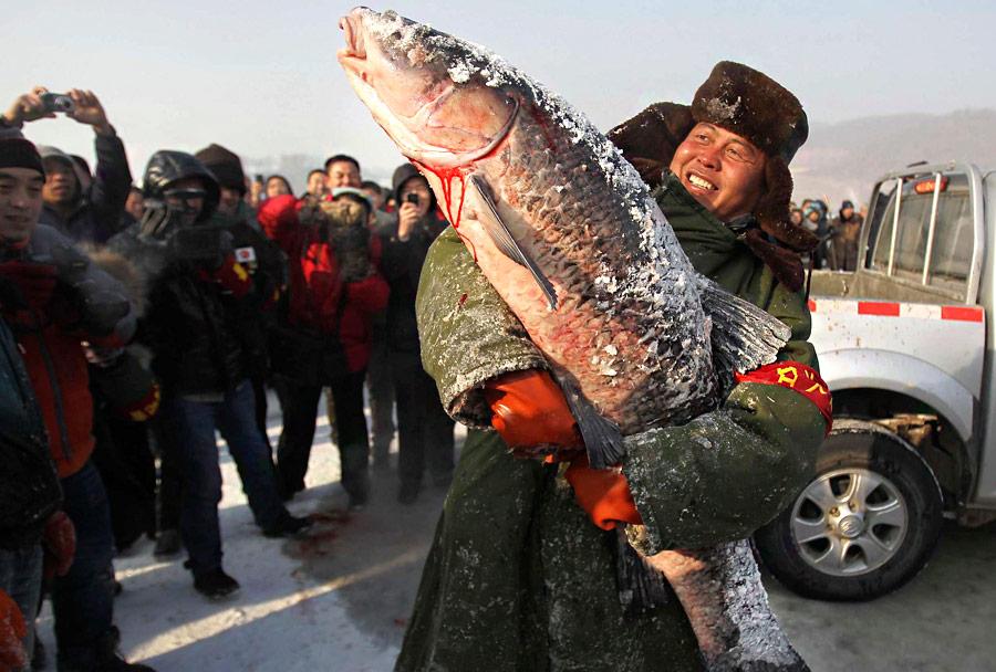 Китаец показывает самую большую рыбу, пойманную входе соревнования позимней рыбалке вЧанчуне. © China Daily/Reuters