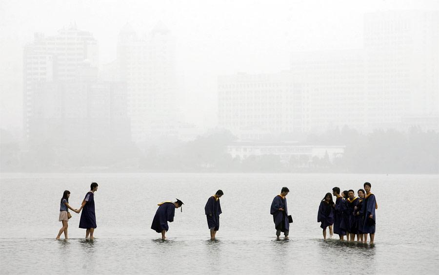 Китайские выпускники назатопленном мосту посреди озера вУхане. © Darley Wong/Reuters