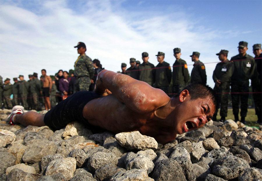 Кандидат вэлитный отряд морской пехоты Тайваня ползет 50-метровую дистанцию поострым камням. © Nicky Loh/Reuters