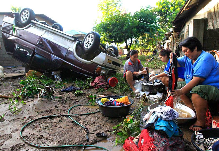 Пострадавшие оттропического шторма «Ваши» наюге Филиппин стирают одежду рядом сперевернутым автомобилем. © Erik DeCastro/Reuters