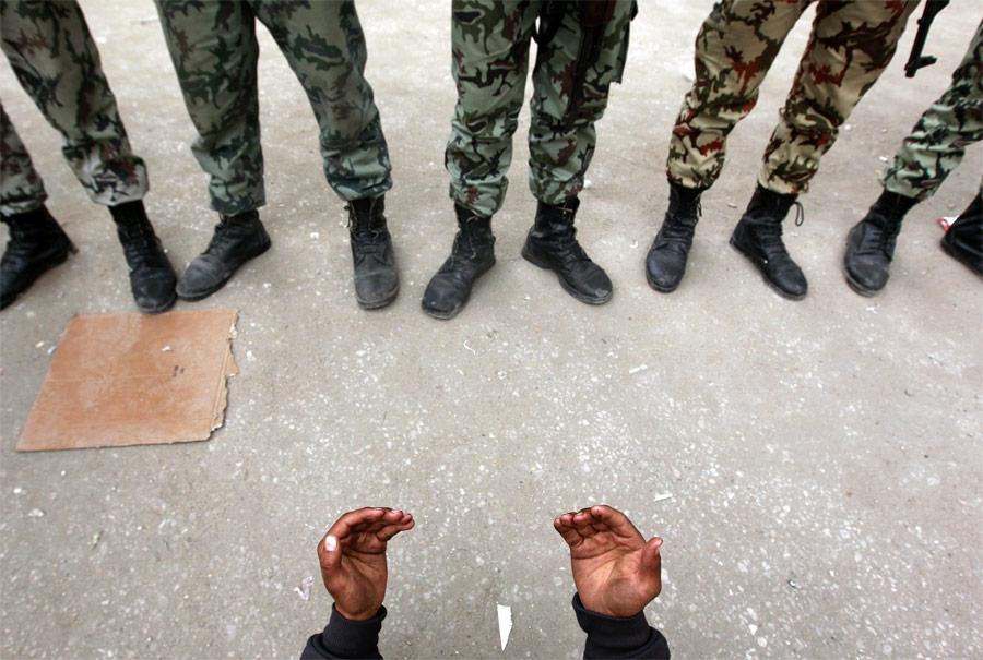 Представитель египетской оппозиции молится перед строем солдат наплощади Тахрир вКаире. © Yannis Behrakis/Reuters
