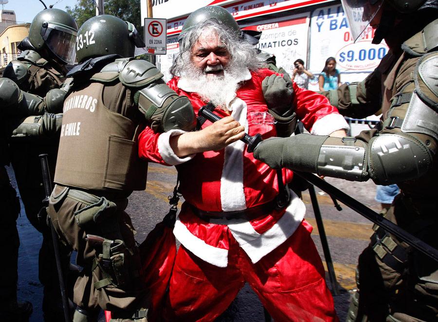 Полиция задерживает одного изпротестантов, одетого вкостюм Санта-Клауса, вовремя акции протеста студентов против существующей системы государственного образования вСантьяго. © Ivan Alvarado/Reuters