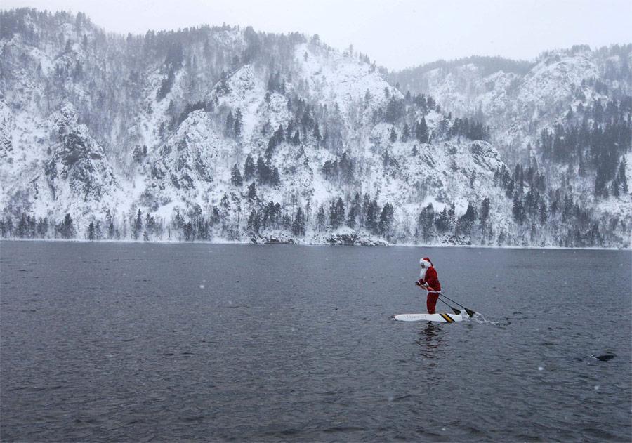 Красноярский учитель Николай Васильев, сконструировавший уникальные водные лыжи, идет наних поЕнисею вкостюме Деда Мороза. © Илья Наймушин/Reuters