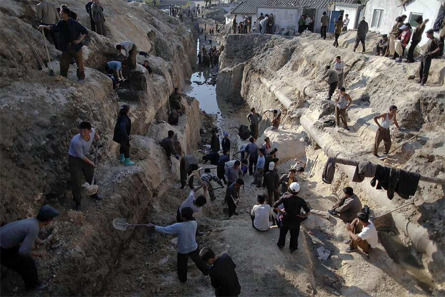 Добровольцы истуденты работают надпочинкой трубопровода вХэджу. © Damir Sagolj/Reuters