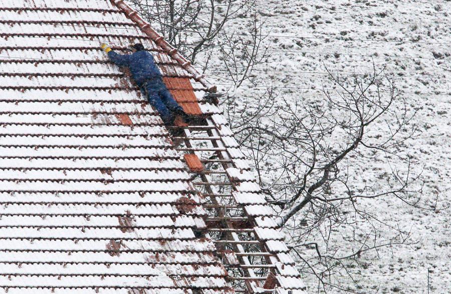 Кровельщик ремонтирует поврежденную крышу дома после шторма впригороде Берна вШвейцарии. © Pascal Lauener/Reuters