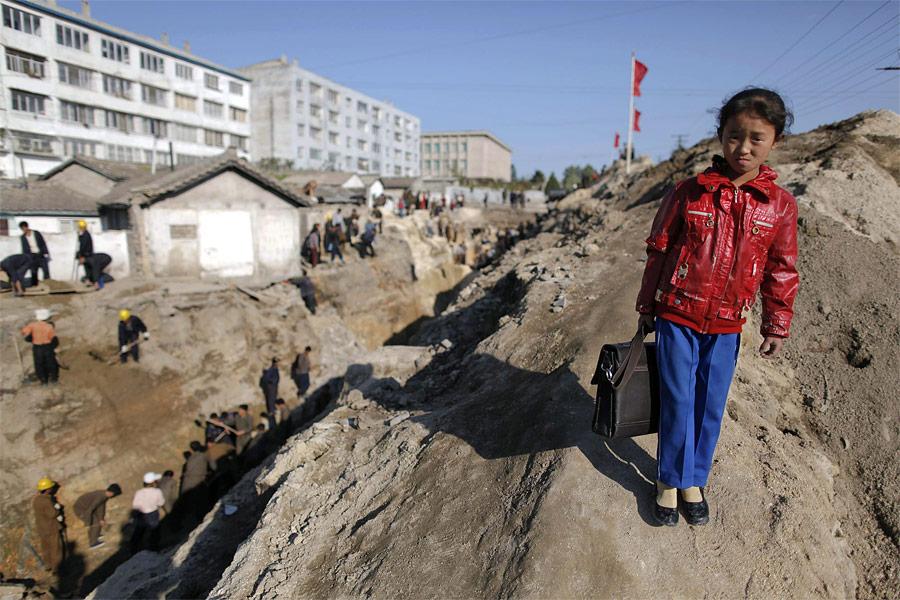 Школьница нафоне масштабных работ поремонту трубопровода вгороде Хэджу. Кремонту трубопровода были привлечены местные студенты идобровольцы. © Damir Sagolj/Reuters
