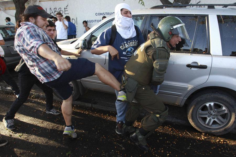 Демонстранты отбивают одного изсвоих сторонников, которого попыталась задержать полиция. © IVAN ALVARADO/Reuters