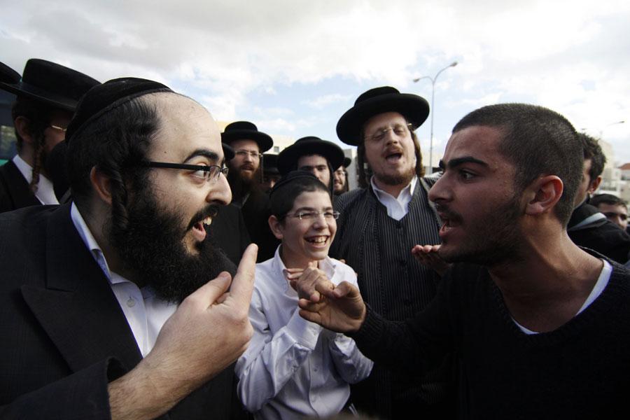 Ортодоксальный еврей спорит сосветским израильтянином вовремя проведения акции протеста. © Reuters