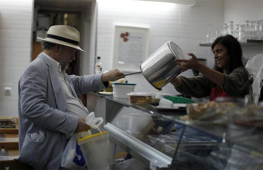 Хантер Халдер забирает остатки еды вкафе. © Rafael Marchante/Reuters