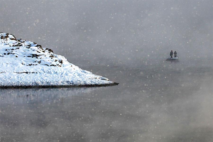 Двое сибиряков втумане переправляются через залив Шумиха наЕнисее в53км кюгу отКрасноярска. © Ilya Naymushin/Reuters