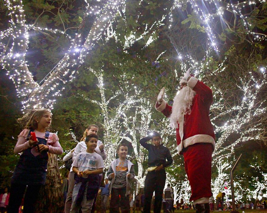 Мужчина вкостюме Санта-Клауса развлекает детей возле наряженных новогодних елок вСан-Паулу. © Nacho Doce/Reuters
