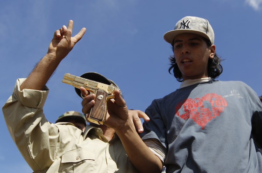18-летний Ахмед Шайбани, убивший Муаммара Каддафи, сзолотым пистолетом диктатора вруках. © Thaier al-Sudani/Reuters