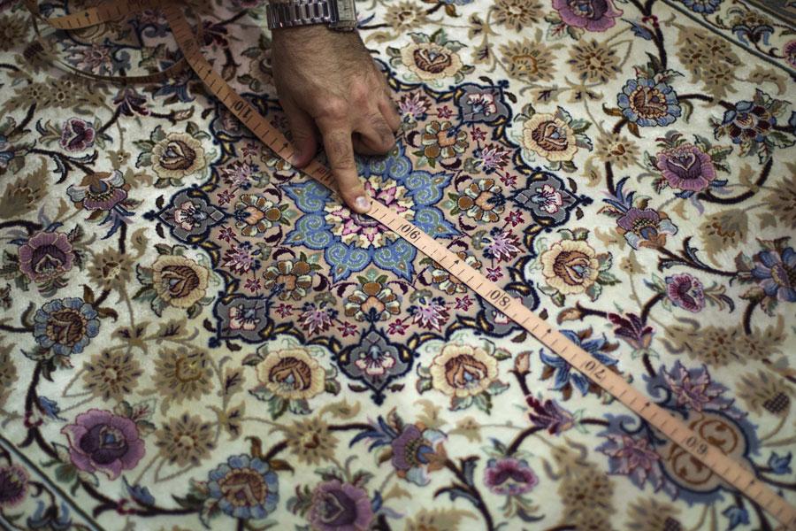 Артин Маркосян, профессор академии искусств Исфахана меряет ковер. © MORTEZA NIKOUBAZL/Reuters