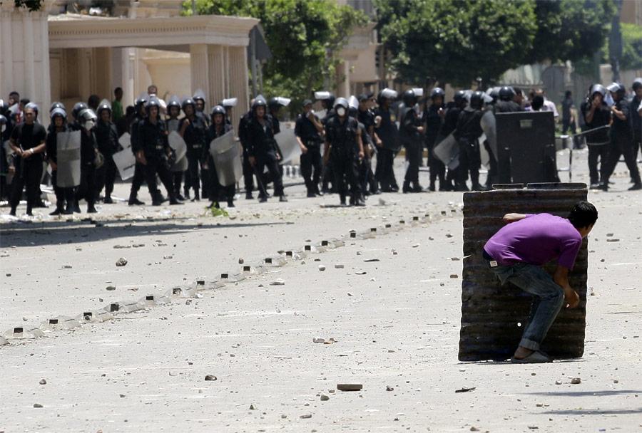 Демонстрант прячется отполиции вовремя столкновений вКаире. © Mohamed Abd El-Ghany/Reuters