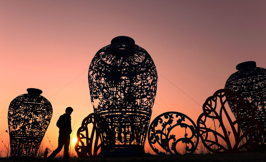 Человек проходит мимо ваз вформе фонарей вкитайском Парке нематериального культурного наследия вовремя фестиваля искусств вХэфее. © Reuters