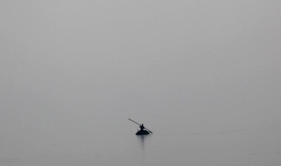 Индийский рабочий чистит отводорослей озеро Дал вШринагаре. © Dar Yasin/AP Photo