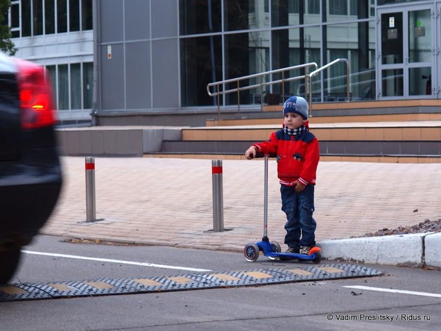 """Мальчик ссамокатом стоит у""""лежачего полицейского, вожидании проезда автомобилей. Парк Сокольники. Москва. © Vadim Preslitsky"""