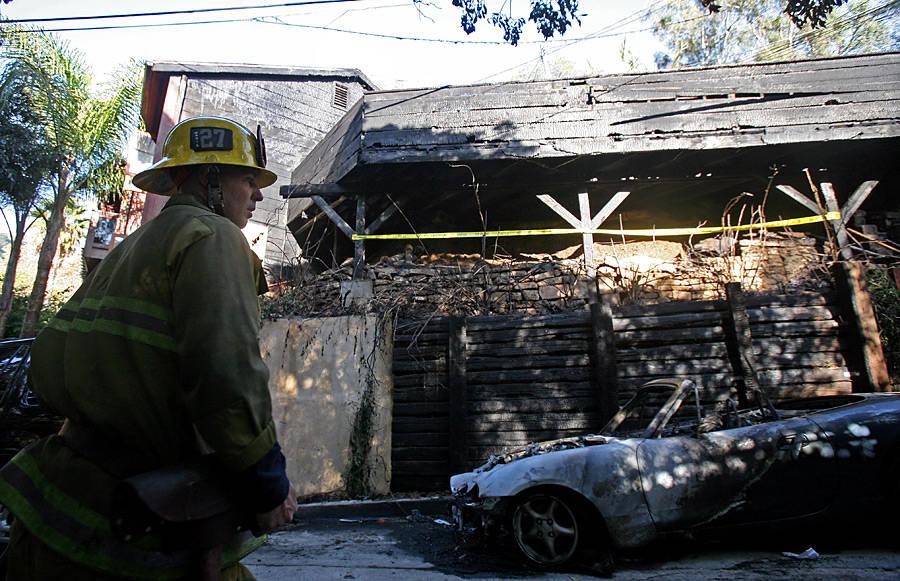 Сотрудник противопожарной службы Лос-Анджелеса усгоревшего автомобиля возле дома Джима Моррисона. © Ringo H.W.Chiu/AP Photo