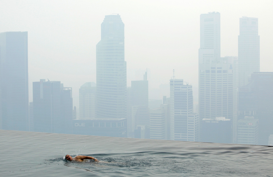 Гость отеля Marina Bay Sands Skypark плавает в бассейне на крыше с видом на Сингапур. © Edgar Su/Reuters
