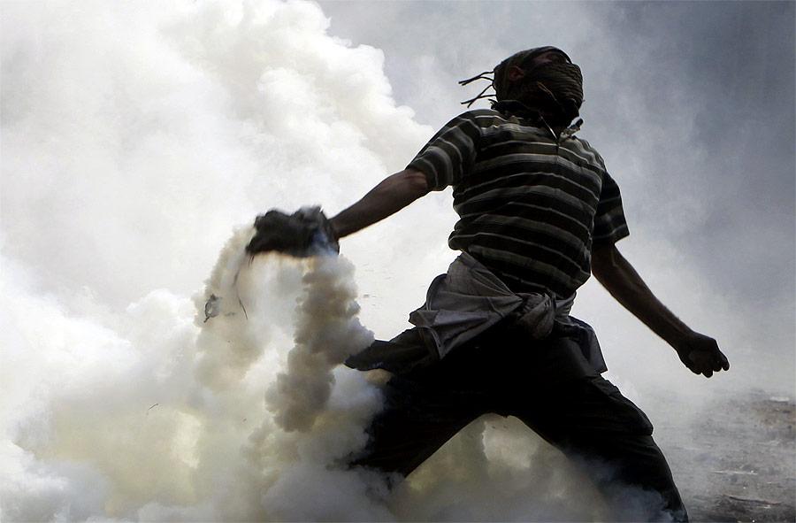 Египетский демонстрант кидает гранату сослезоточивым газом вполицейских, которые ранее кинули эту гранату вдемонстрантов. © Amr Abdallah Dalsh/Reuters