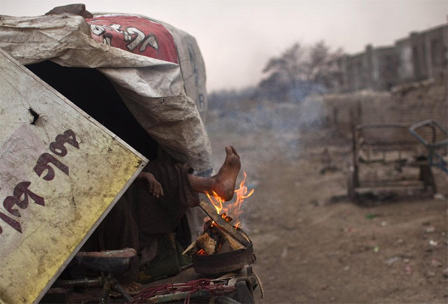 Бездомный пакистанец греет ноги. © Ahmad Masood/Reuters