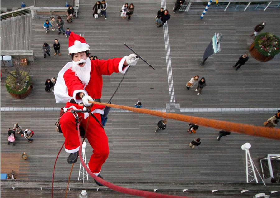 Мойщик окон вкостюме Санта Клауса вовремя мероприятия вчесть предстоящего праздника Рождества вторговом центре вТокио. © Toru Hanai/Reuters