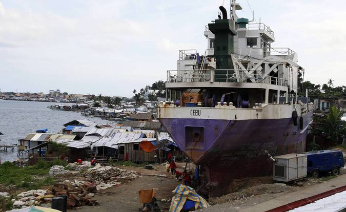 A ship which ran aground during last year's Typhoon Haiyan is pictured next to typhoon victims' temporary shelters in Tacloban city in central Philippines