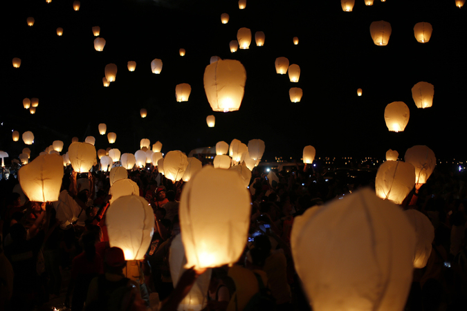 Typhoon survivors, rescuers and aid workers release sky lanterns to commemorate victims who perished during the onslaught of Typhoon Haiyan a year ago in Tacloban city in central Philippines