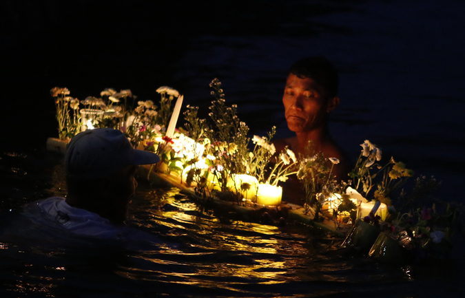 Typhoon survivors bring lighted candles and flowers to the sea to commemorate the victims who perished during the onslaught of Typhoon Haiyan a year ago in Tacloban city, central Philippines