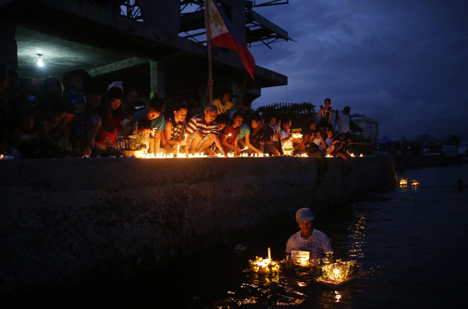 Typhoon survivors light candles outside a damaged local government building and release floating candles to the sea, to commemorate the victims who perished during the onslaught of Typhoon Haiyan a year ago