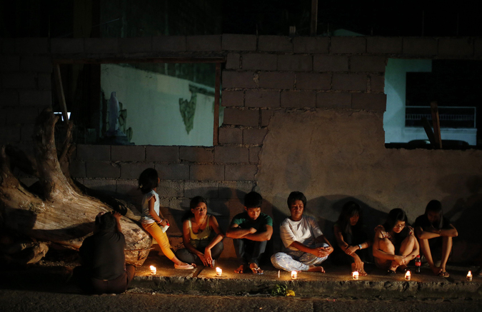 Typhoon survivors light candles outside a typhoon-damaged house being rebuilt, to commemorate victims who perished during the onslaught of Typhoon Haiyan a year ago in Tacloban city, in central Philippines