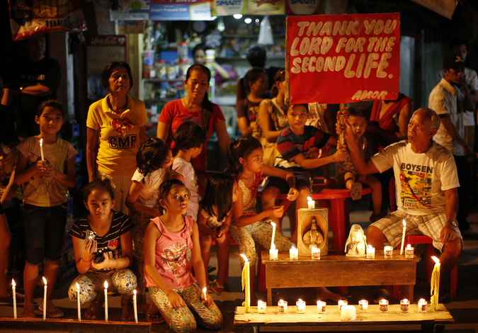 Typhoon survivors light candles along a sidewalk and display a placard to commemorate the victims who perished during the onslaught of Typhoon Haiyan a year ago in Tacloban city, central Philippines
